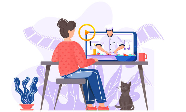 A girl with a cat is sitting at a computer monitor on an online cooking lesson. A male chef on the screen prepares a salad while streaming for master class via the Interner. Video about recipes