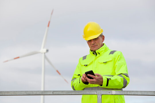 Mature engineer with protective clothing looking at a smart phone in front of a wind turbine