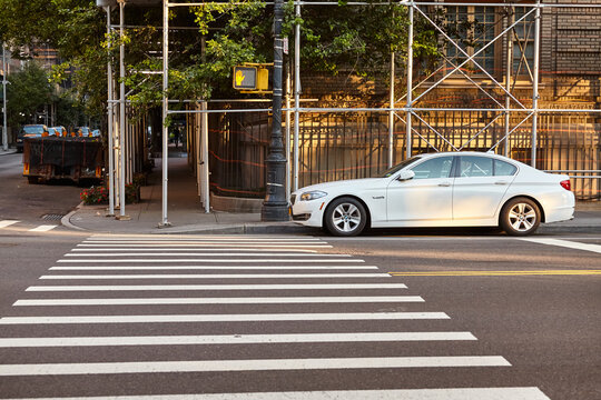New York, USA - July 01, 2018: White BMW vehicle park by a pedestrian crossing in the vicinity of Central Park at sunrise.