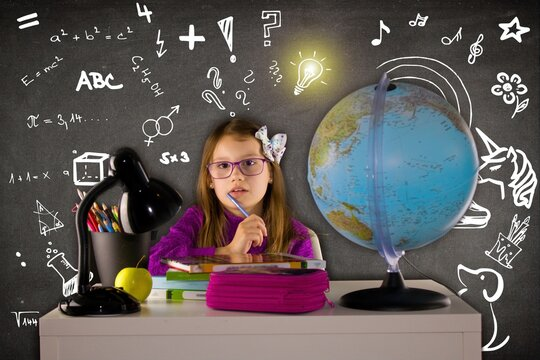 Back to school. Girl with glasses sitting over a pile of textbooks.