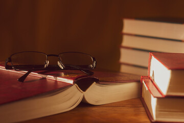 Glasses on an overturned open book against the background of stacks of books. Selective soft focus.