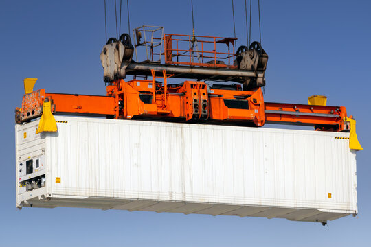 Shipping container lifted by gantry crane in the port.