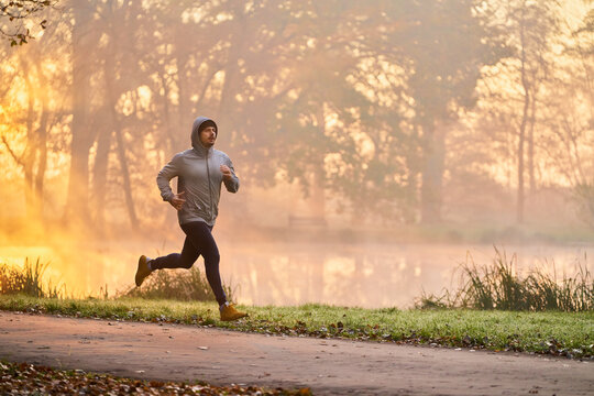 Man jogging in the park during autumn morning