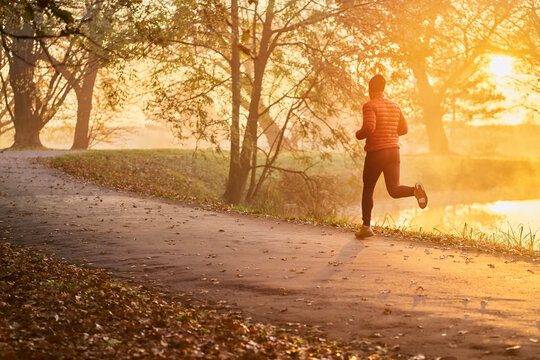Athletic man running in the park during fall autumn morning