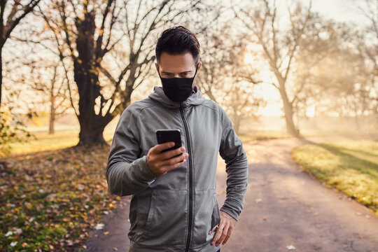 Runner wearing mask checking his mobile phone during autumn run in park