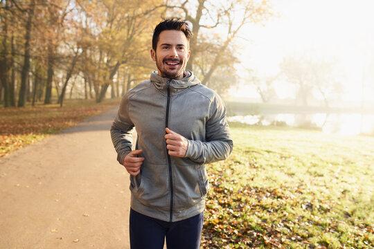 Portrait of man running in park during autumn