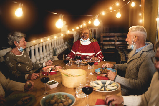 Multiracial senior people celebrate christmas together with dinner outdoor while wearing safety mask for coronavirus outbreak - Soft focus on african woman face