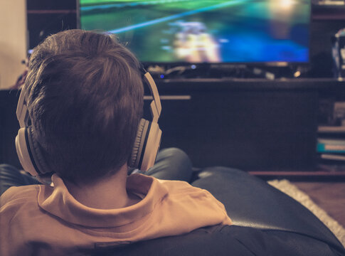 Small boy with headphones watching TV at home. Kid playing video games in the evening.