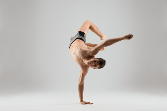 Flexible man dancing breakdance on one hand