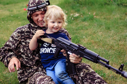 Father and son in camouflage ready to play in laser tag shooting game outside. Concept of father's day, military war game, father's return home.
