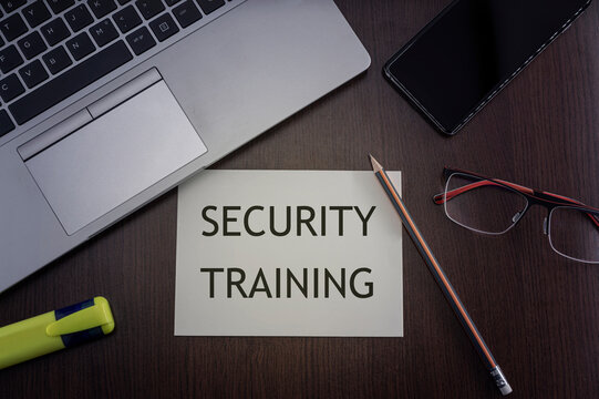 Security training concept. Top view of laptop, phone, glasses and pencil with card with inscription security training.