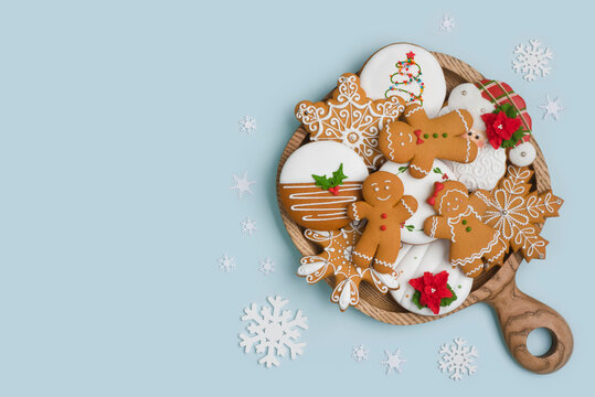 Wooden plate with Christmas homemade gingerbread cookies on blue background