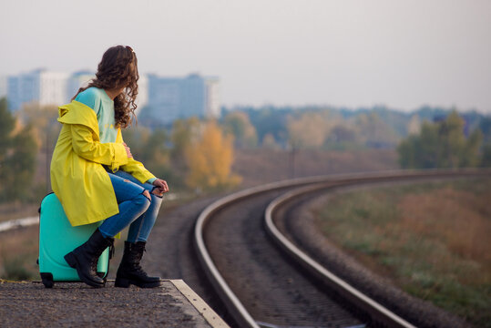 Beautiful young girl in yellow raincoat on a train platform waiting. curly girl in a yellow coat in the fall. No trains, no timetable