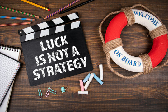 Luck is Not a Strategy. Business concept. Wooden table with office supplies