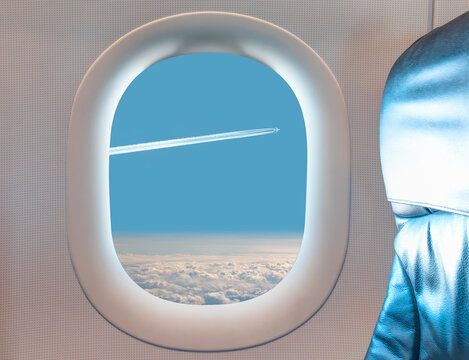 Trail of white smoke from the airplane on blue sky as seen through window of an aircraft