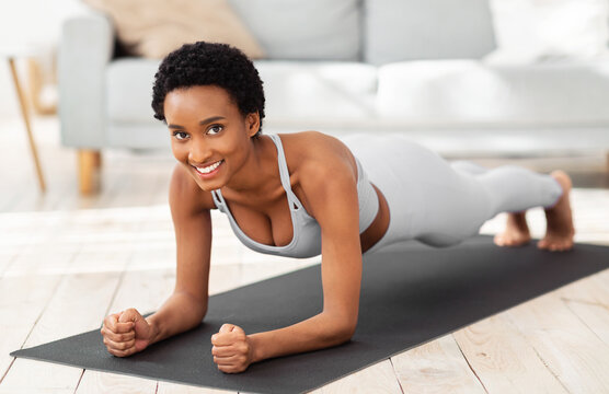 Muscle strengthening exercises. Happy African American woman doing elbow plank, training on yoga mat at home