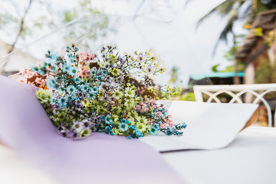 Bouquet of dried multicolor flowers lying on table.