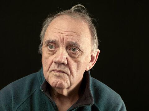 portrait vieil homme amer sur fond noir