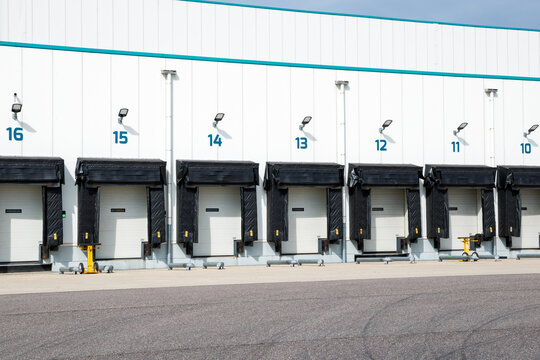 Row of loading docks with shutter doors at an industrial warehouse.