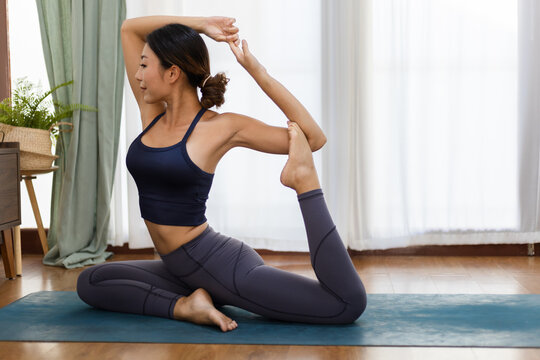 An Asian woman sporty attractive practicing yoga, doing Eka Pada Rajakapotasana pose. Her wearing sportswear and work out at home.