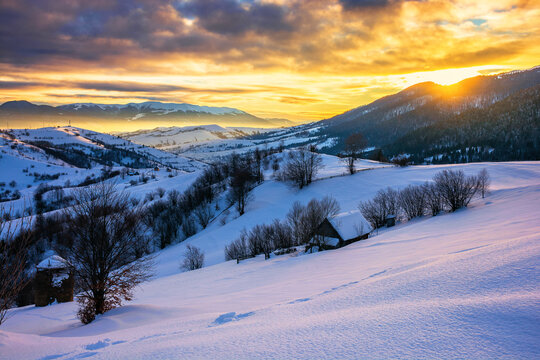 winter landscape in mountains at sunrise. beautiful rural area of carpathian mountains with snow covered hills. glowing clouds on the sky. frosty weather