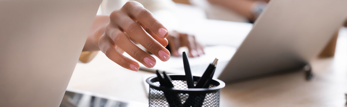 Cropped view of hand of african american woman taking pen from holder on desk on blurred background, banner