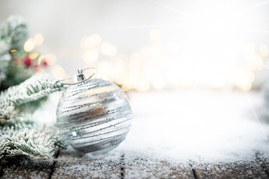 Christmas decorations on snow with christmas balls, fir tree branches and christmas lights. Winter Decoration Background with copy space for text