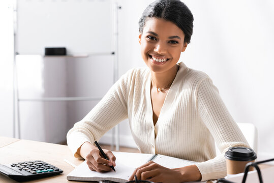 Happy african american woman with pen looking at camera while writing on blank notebook in office on blurred background