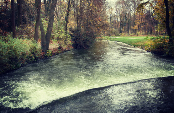 Water canal at Munich Englischer Garten in autumn,beautiful park in the heart of the city  to take a stroll in the nature