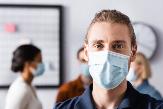 young office manager in medical mask looking at camera near multicultural colleagues on blurred background