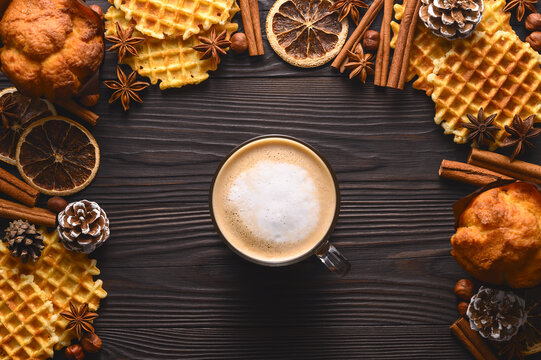 Cup of hot coffee, cookies and spices on wooden rustic background. Stylish cozy winter flat lay. Seasonal holidays concept. Top view