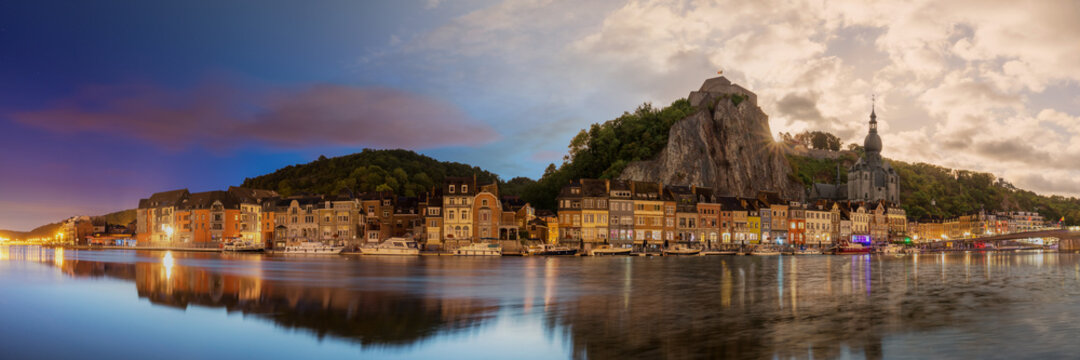 Night to day time blending panorama of the iconic cathedral and rock formation in travel destination Dinant, Belgium