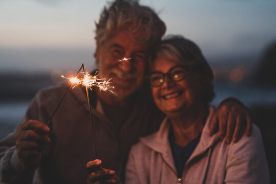 new year. close up of seniors celebrating the new year together at the beach with sparklers lights