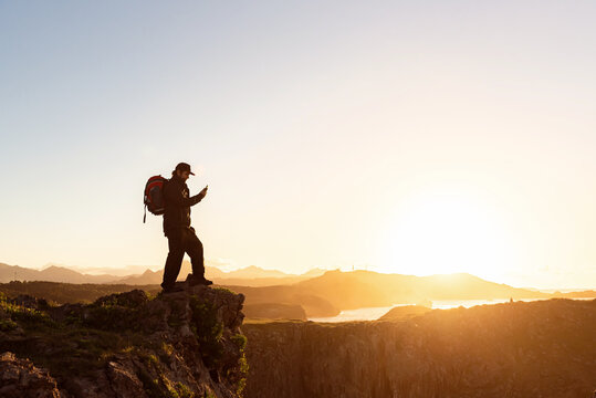 Side view of male explorer with backpack standing on rocky hill and taking photo of spectacular mountainous landscape at sunset