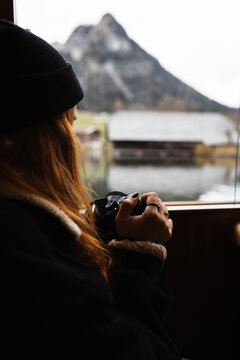 Side view of crop unrecognizable female traveler inserting film roll into old fashioned photo camera during boat trip on lake in autumn day