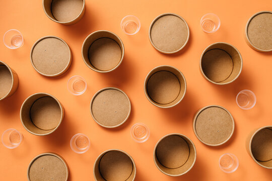 Top view composition of cardboard and plastic cups for takeaway food arranged on orange background