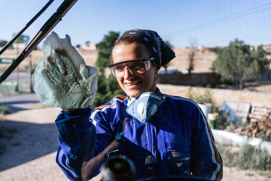 Smiling female worker in uniform and protective glasses cleaning window of machine in industrial area