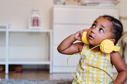 Adorable little African American girl in dress sitting at home and listening to music in headphones while looking up