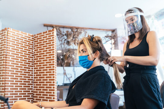 Side view low angle of female hairdresser in face shield and mask making hairdo for customer while working in salon during coronavirus pandemic