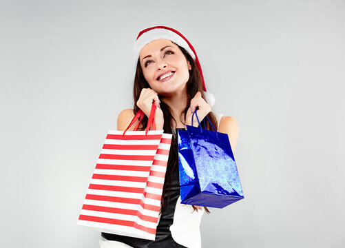 Happy enjoying woman in Santa Claus hat holding Christmas present packages and happy dreaming looking up. Portrait