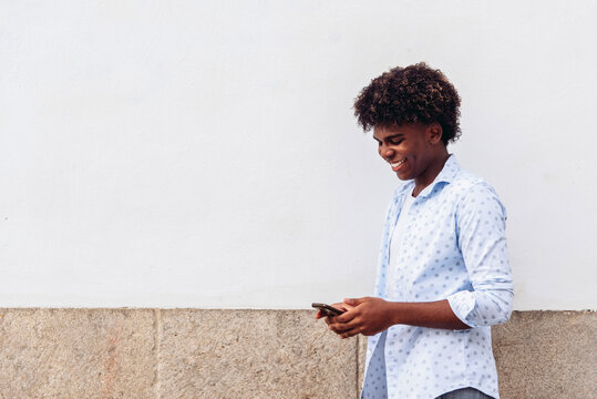 Side view of smiling African American male standing near urban building in city and surfing Internet on cellphone