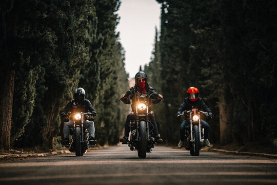 Group of bikers in black leather jackets and helmets riding powerful motorcycles on asphalt road leading between green forest in countryside