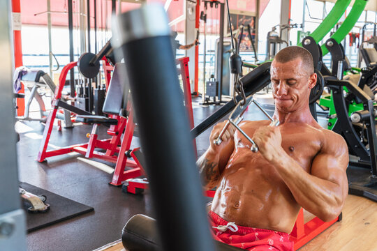 Muscular male bodybuilder with naked torso pulling cable of training machine in modern sports center during active workout