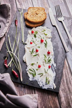 From above of tasty cream cheese and pieces of fresh bread arranged with various herbs on slate board on wooden table