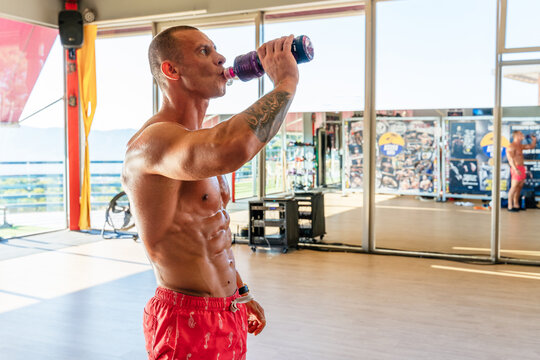Side view of sweaty sportsman with naked torso standing in gym and enjoying fresh water from bottle while having break during workout
