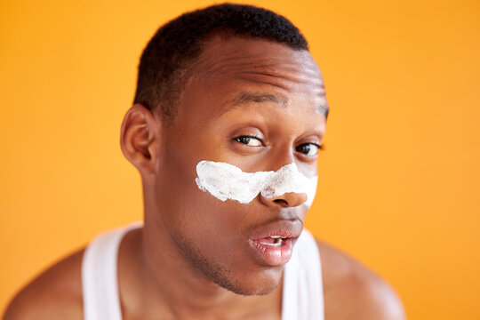 beauty procedure and skin care, young black manful man with face mask on around nose zone, isolated over yellow background