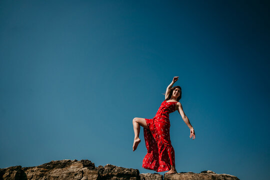 From below low angle side view of barefoot female in long red dress moving gracefully and balancing on leg on rough hill