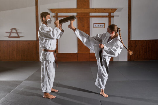 Woman with braid wearing protective mask and white kimono with a black belt attached kicking a man's mitten into the air
