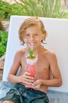 Cheerful preteen boy with wet curly hair sitting on chair and enjoying refreshing fruit drink while spending summer day at poolside in resort