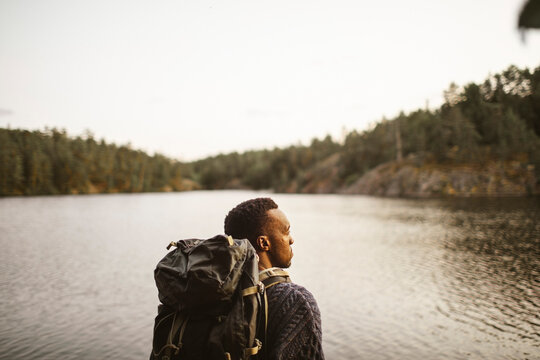 Rear view of man with backpack looking away against lake in forest